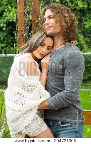 Happy couple in love at outdoors, leaning on her boyfriend's chest in a patio backyard background.