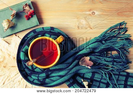Fall background. Cup of tea old book and warm scarf on the wooden background. Fall still life. Concept of spending fall time at cozy home. Vintage fall still life. Fall concept