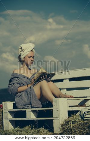 Woman reading book on bench. Girl in bathrobe and towel on head. Student sunbathing on sunny day on natural background. Summer holidays and vacation. Spa and wellness concept.