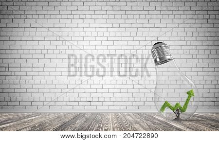 Glass lightbulb with growing green arrow graph inside in empty room with grey brick wall on background. 3D rendering.