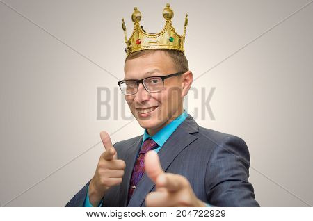 Winner. Award ceremony. First place man. Top manager. Young successful business man in suit and glasses with golden crown on his head showing success symbol. Vip client. Premium user. Success.
