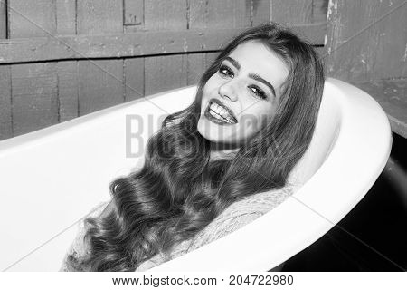 Closeup view of one attractive happy smiling sexy sensual playful young woman with long curly hair lying in white bath tub indoor on wooden background horizontal picture