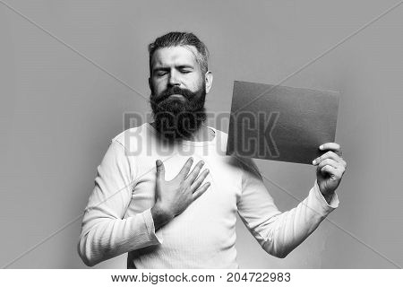young bearded man with serious face holding red paper sheet in studio on grey background copy space