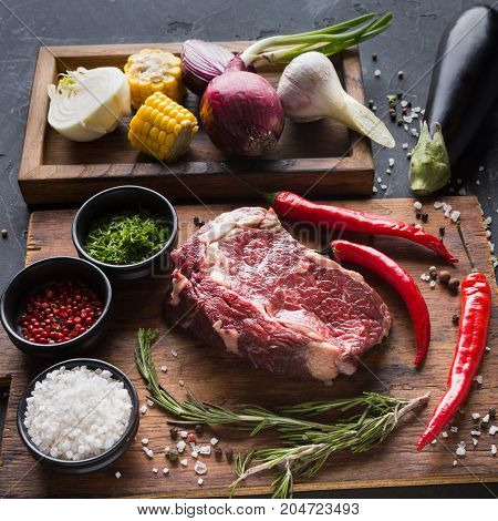 Raw rib eye steak with herbs. Fresh meat with chilli on wooden desk. Cooking ingredients for restaurant dish in a wooden box with onions and corn, closeup