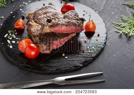 Rare rib eye steak on dark plate decorated with tomatoes, spices and meat fork, closeup
