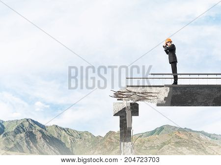 Young engineer in suit and helmet looking in binoculars while standing on broken bridge with skyscape on background. 3D rendering.