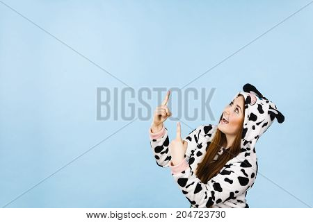 Happy teenage girl in funny nightclothes pajamas cartoon style pointing up with positive surprised face expression studio shot on blue. Advertisement concept