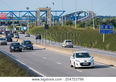 LE HAVRE FRANCE - AUGUST 24 2017: Toll station with passing cars at bridge Pont de Normandie over river Seine