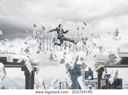 Businessman jumping over gap with flying paper documents in concrete bridge as symbol of overcoming challenges. Cityscape on background. 3D rendering.