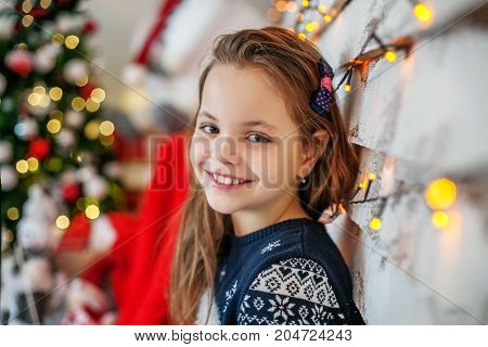Happy Child student sitting near the Christmas tree. The concept of Merry Christmas New Year family.
