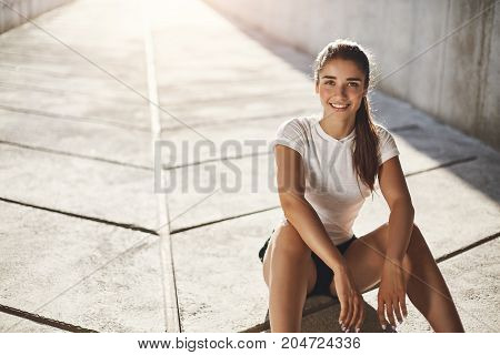 Fit teenage girl looking at camera preparing for her everyday morning workout. Urban sport concept.