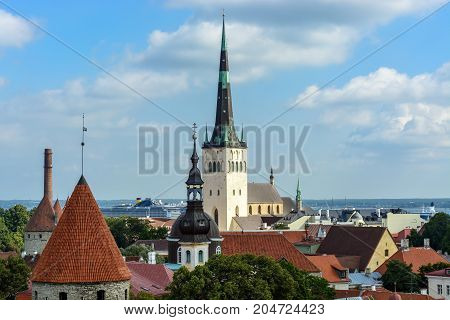 Panorama of old Tallinn with a view of the church of Saint Olaf against the blue sky with white clouds.