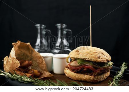Craft beef burger wooden table on dark blue background.