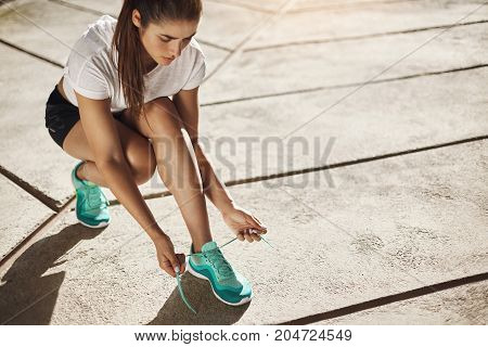 Woman runner tying up her laces getting ready for a long run into successful fitness career. Urban sport concept.