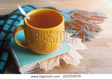Autumn still life. Cup of tea, worn book with dry maple autumn leaf, green scarf on the wooden background - autumn still life. Autumn background. Autumn concept. Vintage autumn still life. Autumn composition.