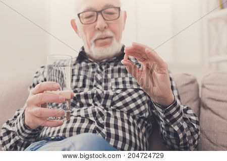 Old man having a glass of water and pills in hand. Healthcare, treatment, aging concept