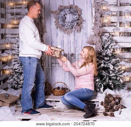 Studio shot of two people at doorstep during winter holidays. Man gives woman present.