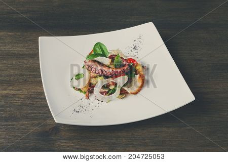 Salad with octopus and vegetables top view. Appetizing fresh mediterranean seafood meal with toasts, restaurant serving