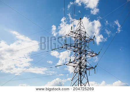 Power tower over blue summer sky. Electric wires. Electrical power. The power of nature. The power of modern technology.