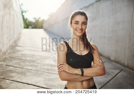 Portrait of young female sports enthusiast standing confident ready for usual city workout. Staying fit in urban environment.