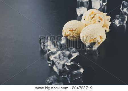Ice cream scoops with ice cubes on black background. Delicious cold sweet dessert, copy space