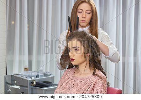 Young female at the hairdresser. Stylist with hair straightener.