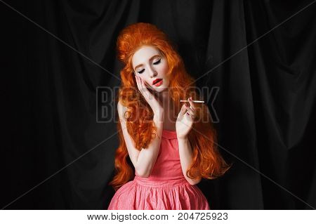 A smoking with cigarette woman with pale skin and long curly red hair in a pink dress on a black background. Beautiful girl with red lips with a cigarette in her hands. Beauty makeup. Redhead model with cigarette. Sensual portrait of model with cigarette