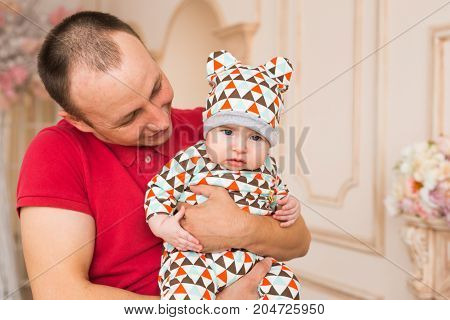 Adorable Caucasian baby and his father. Portrait of a three months old baby boy.
