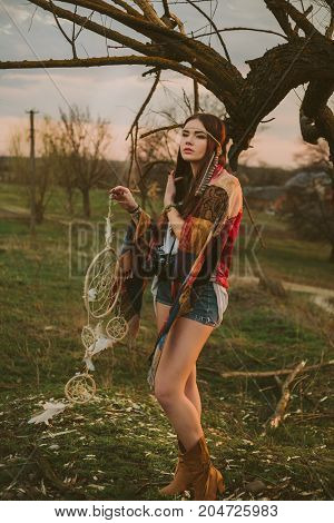 hipster girl standing near an old tree. the girl is holding the dreamcatcher.