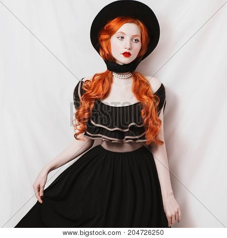 Red-haired edwardian retro girl in a black edwardian dress on a white background. Edwardian woman with pale skin. Edwardian model on white background.