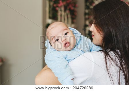 Loving Asian Mother Holding Baby Son At Home.