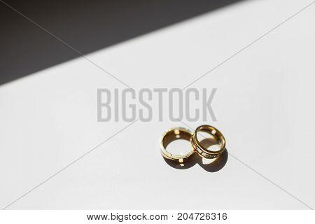 Wedding rings lie on a window on a dark white background. Yellow wedding ring. Two wedding rings. The rings lie on the window. Two wedding rings.