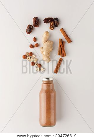 Healthy food. Detox smoothie with ingredients, cinnamon, ginger, dried fruits and nuts, on white background, top view, copy space.