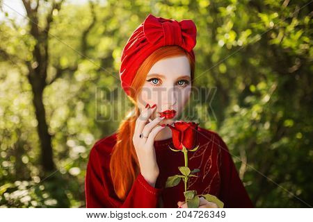 A retro woman with pale skin and long red hair a red retro dress and a  retro turban on a summer background. A retro girl with red nails and a rose in her hand. Retro model