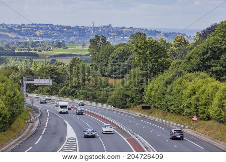 Moderate traffic on a highway between the forests in NormandyFrance.