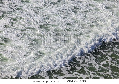 Aerial view of the foamy ocean surface wiht a crashing wave.