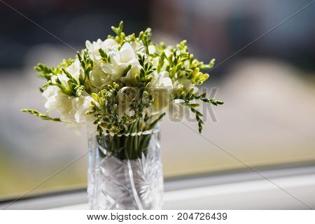 Wedding bouquet of white flowers on a light background. Bridal bouquet. Bouquet of flowers. White bouquet A bouquet is standing on the window.