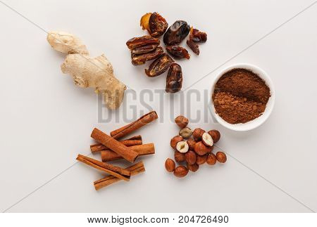 Healthy food. Ingredients for detox smoothie, cinnamon, ginger, nuts, on white background, top view, copy space.