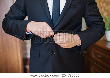 A stylish business man in a dark jacket. The business man in a respectable suit button up his buttons. Business concept. Business meeting. Business offer. Conceptual picture of a business man in suit