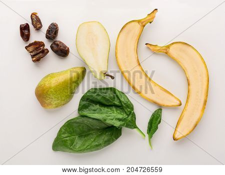 Healthy food. Ingredients for detox smoothie, banana, pear, spinach, dates on white background, top view, copy space.