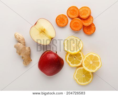 Healthy food. Ingredients for detox smoothie, ginger, carrot, apple, lemon on white background, top view, copy space.