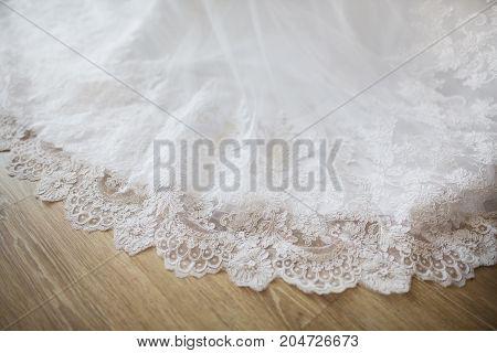 The hem of the wedding dress lies on the wooden floor. Wedding wear. Wedding gown. Going to the wedding. Wedding invitation