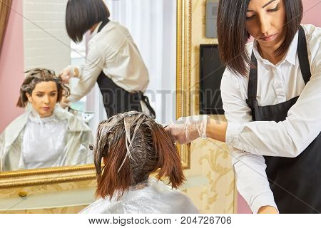 Beautician and client, hair dying. Inside beauty salon. Become a hair color specialist.