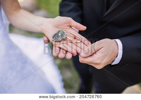 The bride and groom hold a lock in their hands. Celebrate the wedding. Wedding ceremony near the wedding arch. Lock and key. Groom with lock. To hold a lock