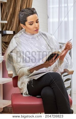 Girl in hair salon reading. Young woman holding a magazine. Top news magazines.
