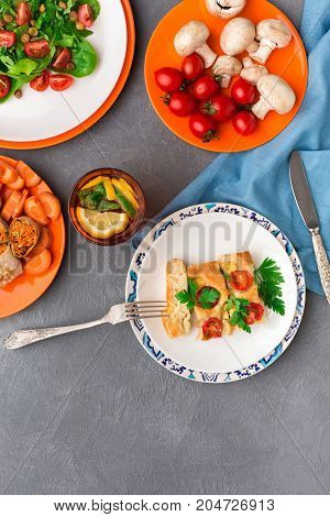 Healthy eating concept. Casserole with tomatoes, fresh salad with greens and lemonade on gray background. Organic vegetables top view, copy space