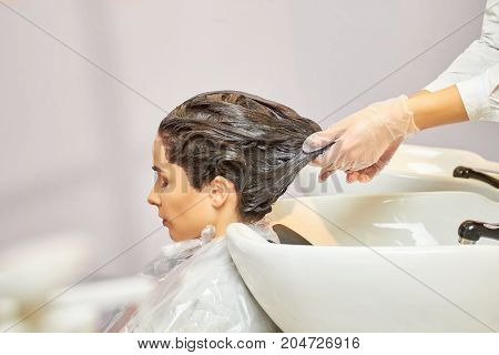 Hair dying process in salon. Hands of beautician near sink.