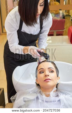Female getting her head washed. Beautician rinsing hair of client.