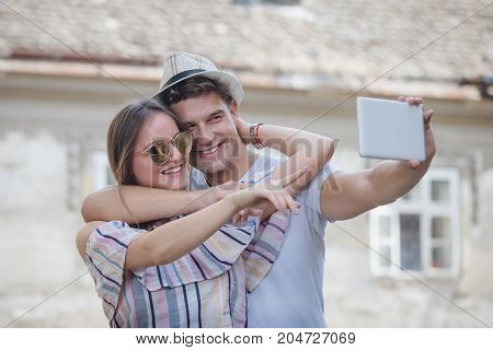 Young hipster tourist couple taking selfie with digital tablet device outdoors. Love and technology concepts