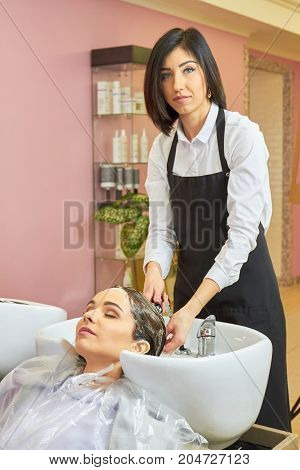 Beautician washing head of customer. Woman working in hair salon. Shampoo recommended by stylists.